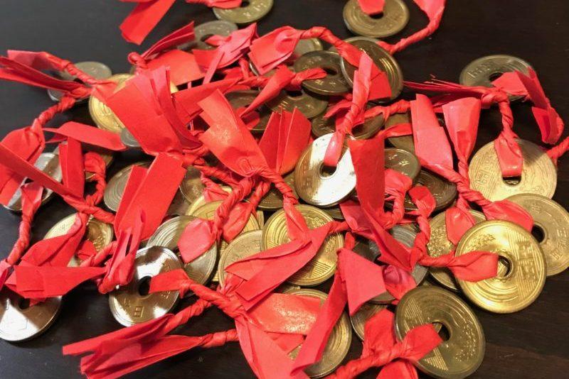 真っ赤な紙の紐を結んだ5円玉